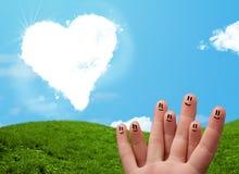 Doigts souriants heureux regardant le nuage en forme de coeur Photos stock