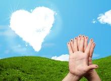 Doigts souriants heureux regardant le nuage en forme de coeur Image stock