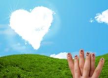 Doigts souriants heureux regardant le nuage en forme de coeur Photographie stock