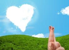 Doigts souriants heureux regardant le nuage en forme de coeur Photo libre de droits