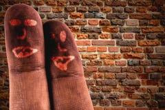 Doigts tristes contre le mur de briques Photos stock