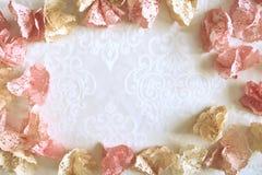 Doilies de papel cor-de-rosa e amarelos em uma toalha de mesa branca Fotos de Stock