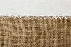 Doily on burlap. Doily with handmade lace on burlap texture royalty free stock photography