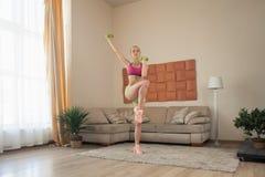 Doin femenino deportivo joven que estira en casa Fotografía de archivo