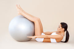 Doing abdominal muscles with fitness ball. Cute woman doing abdominal muscles with fitness ball Royalty Free Stock Images