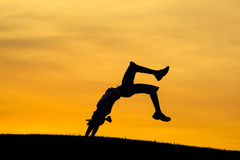 Doing a back bend at sunset. Stock Photography