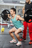 Doing barbell squats with personal instructor Stock Photos