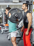 Doing barbell squats with personal instructor Royalty Free Stock Image