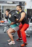 Doing barbell squats with personal instructor Royalty Free Stock Photography