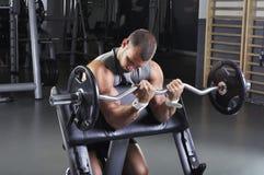 Doing Biceps Exercise di modello maschio muscolare bello Fotografie Stock Libere da Diritti
