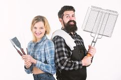 Doing a big BBQ at the weekend. Sexy woman and bearded hipster holding cooking grate. Happy couple using grid for royalty free stock images