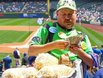 Doing Big Business As a Stadium Food Vendor. A hard working food vendor at the Seattle Mariners Safeco Baseball Field intensely counts his wad of greenback cash Stock Photography