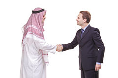 Doing business. An Arab person shaking hands with a businessman Stock Photos