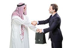 Doing business. Arab person shaking hands with a businessman isolated on white royalty free stock photography