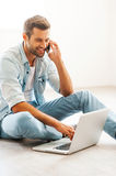 Doing business at home. Smiling young man working on laptop and talking on the mobile phone while sitting on the floor at his apartment Royalty Free Stock Images