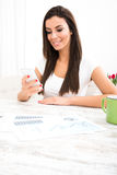 Doing business at home. A young woman doing business at home and using her smartphone Stock Images