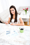 Doing business at home. A young woman doing business at home and using her smartphone Royalty Free Stock Photography
