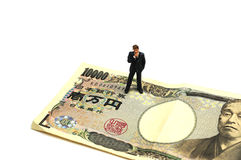 Doing business in Japan. A businessman standing on a japanese banknote Royalty Free Stock Photo