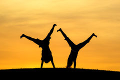 Doing cartwheels together. Royalty Free Stock Image