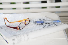Doing a crossword. An almost completed crossword with a ballpoint pen and a pair of spectacles Stock Image