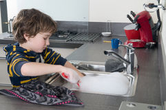 Doing the dishes. Boy doing the dishes in a modern kitchen Stock Photo