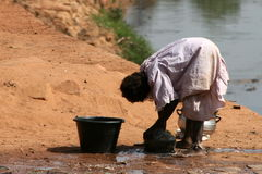 Doing the dishes. African women doing the dishes near a river Stock Image