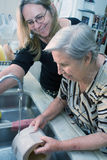 Doing Dishes. Woman and her elderly mother doing dishes together in the kitchen Stock Photo