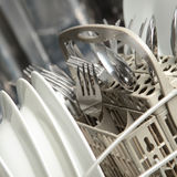 Doing the Dishes. A full dishwasher with clean dishes. Shallow DOF, focus on the utensils Royalty Free Stock Image