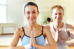 Doing exercise. Photo of happy girl and young man with hands kept in touch Royalty Free Stock Image