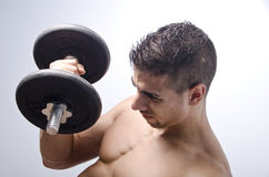 Doing exercise with weights. Young boy lifting weights, on blue background Stock Photo