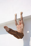 Doing exercise. Young sportsman doing exercise near white wall with naked torso Stock Image