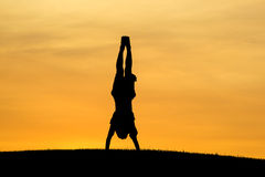 Doing a hand stand at sunset. Royalty Free Stock Image
