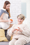 Doing her hobby in good company. Elderly women doing knitwork accompanied by her granddaughter Stock Photography
