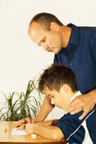 Doing homework. Boy doing homework while father helps royalty free stock photos