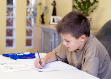 Doing homework. A boy sitting at a table in the living room, doing his homework Stock Image