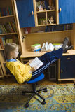 Doing homework. Young girl wearing yellow blouse sitting at the desk Stock Photos