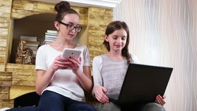 Doing homework with classmate at home, girls sitting together on carpet and using laptop and tablet stock video
