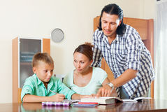 Doing homework in home interior. Ordinary family of three doing homework in home interior Royalty Free Stock Photos