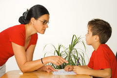 Doing homework with mother. Boy doing homework while mother helps stock photography