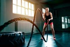 Doing intense hard training with rope at gym. Woman training with battle ropes in gym, doing intense hard training stock photo