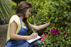 Doing inventory in a garden. Young female gardener taking notes and doing inventory at work Stock Images