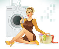 Doing Laundry. Beautiful woman sitting next to a washing machine and a pile of laundry Stock Images