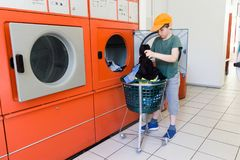 Doing the laundry in a laundromat salon Stock Images