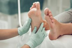 Skilled experienced beauty master working in rubber gloves. Doing leg massage. Skilled experienced beauty master working in rubber gloves and massaging feet of stock photography