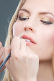 Doing lips makeup with a brush Royalty Free Stock Image
