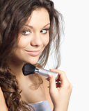 Doing makeup. Beautiful young woman doing makeup isolated on white Stock Photography