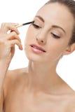 Doing the makeup brown eyeshadow on beautiful eyes Stock Photo