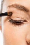 Doing the makeup brown eyeshadow on beautiful eyes Stock Image
