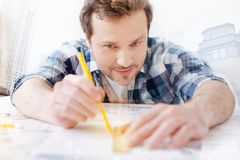 Talented engineer using a pencil and a ruler. Doing my best. Close up of talented engineer leaning on the table wile drawing a sketch using a ruler and a pencil Royalty Free Stock Photography