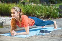 Doing plank outdoors. Beautiful and sporty woman doing plank outdoors Royalty Free Stock Photos